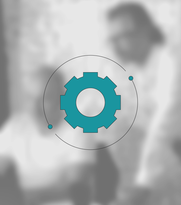 Pictogram of a hexagon socket head cap screw in the colour petrol blue surrounded by two arches, which is to represent the company as a service provider. The pictogram lies on a blurred image showing two employees of the company.