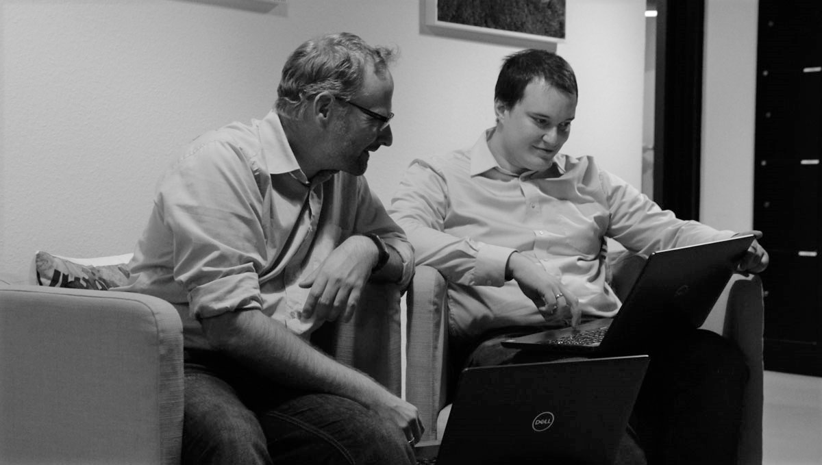 Two developers from Brinkmann Electronic Berlin GmbH, each with a laptop, are in a meeting.