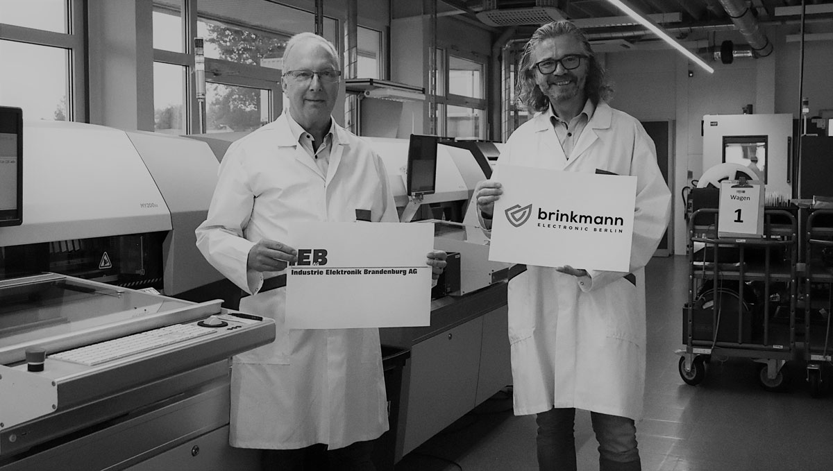 Hans Marold and Peter Brinkmann are standing in front of machines and holding signs with their company logos
